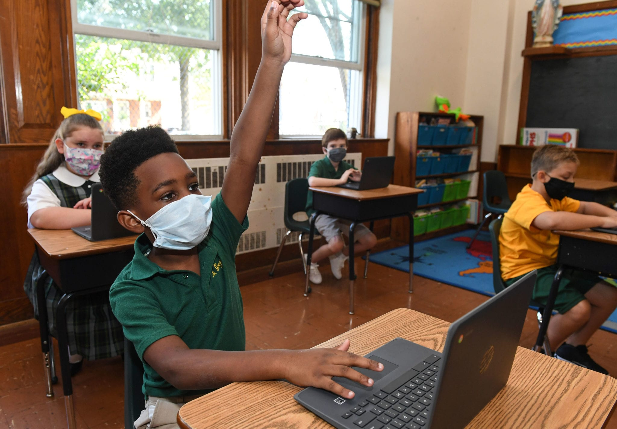 Children Being Safe in the classroom wearing masks and using chrome books